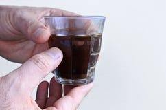 Τα χέρια ατόμων κρατούν ένα μαύρο φλυτζάνι καφέ Στοκ εικόνα με δικαίωμα ελεύθερης χρήσης