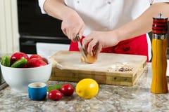 Τα χέρια ατόμων κόβουν το κρεμμύδι με το μεγάλο μαχαίρι Στοκ Εικόνες