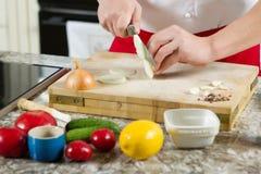 Τα χέρια ατόμων κόβουν το κρεμμύδι με το μεγάλο μαχαίρι Στοκ εικόνα με δικαίωμα ελεύθερης χρήσης