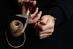 Τα χέρια ατόμων κόβουν το σχοινί με το ψαλίδι Στοκ Εικόνες