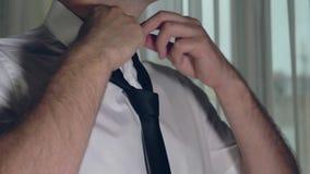 Τα χέρια ατόμων χαλαρώνουν τον κόμβο του δεσμού γύρω από το λαιμό που ντύνεται στο πουκάμισο απόθεμα βίντεο