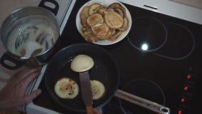 Τα χέρια ατόμων ` s αναποδογυρίζουν τις τηγανίτες στο τηγάνισμα του τηγανιού απόθεμα βίντεο