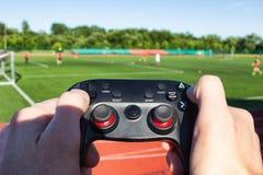Τα χέρια ατόμων ` s κρατούν ένα πηδάλιο παιχνιδιών και πιέζουν τα κουμπιά στο υπόβαθρο του σταδίου στο οποίο παίζουν το ποδόσφαιρ στοκ εικόνες με δικαίωμα ελεύθερης χρήσης