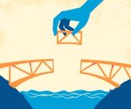 Τα χέρια βάζουν το τελευταίο κομμάτι για να ολοκληρώσουν τη γέφυρα απεικόνιση αποθεμάτων