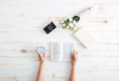 Τα χέρια γυναικών αναποδογυρίζουν τις σελίδες βιβλίων στο ξύλινο γραφείο Στοκ εικόνες με δικαίωμα ελεύθερης χρήσης