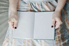 Τα χέρια γυναικών κρατούν το κενό κενό βιβλίο, τοπ άποψη, σχετικά με τη φούστα Στοκ φωτογραφίες με δικαίωμα ελεύθερης χρήσης