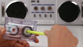 Τα χέρια γυναικών ξανατυλίγουν μια ακουστική κασέτα χρησιμοποιώντας μια μάνδρα φιλμ μικρού μήκους