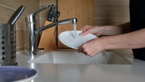 Τα χέρια γυναικών ξεπλένουν το πιάτο στο νεροχύτη κουζινών - κάνοντας τις μικροδουλειές στο σπίτι Στερεότυπη, στατική κάμερα πλύσ απόθεμα βίντεο