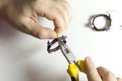 Τα χέρια γυναικών που κάνουν το floral κόσμημα από τον πολυμερή άργιλο, καλλιτέχνης κάνουν τα χειροποίητα σκουλαρίκια με τα πορφυ Στοκ εικόνα με δικαίωμα ελεύθερης χρήσης