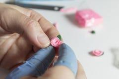 Τα χέρια γυναικών που κάνουν το floral κόσμημα από τον πολυμερή άργιλο, καλλιτέχνης κάνουν τα χειροποίητα σκουλαρίκια με τα ροδαλ Στοκ εικόνες με δικαίωμα ελεύθερης χρήσης
