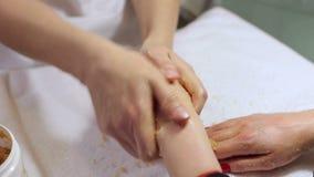 Τα χέρια γυναικών που λαμβάνουν ένα χέρι τρίβουν την αποφλοίωση από ένα beautician στο σαλόνι ομορφιάς φιλμ μικρού μήκους