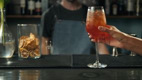 Τα χέρια γυναικών που ψήνουν με τα κοκτέιλ aperol spritz, γυναίκα στο φραγμό παίρνουν το οινόπνευμα από bartender απόθεμα βίντεο