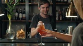 Τα χέρια γυναικών που ψήνουν με τα κοκτέιλ aperol spritz, γυναίκα στο φραγμό παίρνουν το οινόπνευμα από bartender φιλμ μικρού μήκους