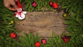 Τα χέρια γυναικών ` s δημιουργούν ένα ντεκόρ Χριστουγέννων Κλάδοι χριστουγεννιάτικων δέντρων με τους κώνους και διακοσμήσεις Χρισ απόθεμα βίντεο