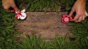 Τα χέρια γυναικών ` s δημιουργούν ένα ντεκόρ Χριστουγέννων Κλάδοι χριστουγεννιάτικων δέντρων με τους κώνους και διακοσμήσεις Χρισ φιλμ μικρού μήκους