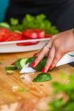 Τα χέρια γυναικών ` s κόβουν τα φρέσκα λαχανικά στοκ φωτογραφία