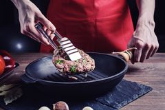 Τα χέρια γυναικών ` s με τις λαβίδες αναποδογυρίζουν ένα ακατέργαστο κομμάτι του βόειου κρέατος με τα χορτάρια σε ένα τηγάνι χυτο στοκ εικόνα