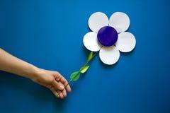 Τα χέρια γυναικών ` s που κρατούν το έγγραφο ανθίζουν με το μεταλλικό εμπορευματοκιβώτιο βάζων κρέμας στο μπλε υπόβαθρο εγγράφου  Στοκ Εικόνες
