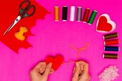 Τα χέρια γυναικών ` s ράβουν ένα μαξιλάρι υπό μορφή καρδιάς σε έναν ρόδινο πίνακα Υπόβαθρο βαλεντίνων με τις χειροποίητες ραμμένε Στοκ Εικόνα