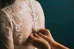 Τα χέρια γυναικών ` s στερεώνουν με τα κουμπιά στο πίσω μέρος μιας όμορφης άσπρης κινηματογράφησης σε πρώτο πλάνο φορεμάτων γαμήλ στοκ εικόνες