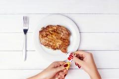 Τα χέρια γυναικών ` s ωθούν την πραγματική μπριζόλα κρέατος από το σωλήνα Στοκ Εικόνες