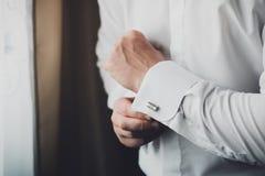 Τα χέρια διορθώνουν τα στερεώνοντας πουκάμισα φορεμάτων μανσετών άσπρα, νεόνυμφος στοκ φωτογραφία
