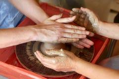 Τα χέρια δύο ανθρώπων δημιουργούν το δοχείο, ρόδα αγγειοπλαστών ` s Αγγειοπλαστική διδασκαλίας Στοκ φωτογραφίες με δικαίωμα ελεύθερης χρήσης