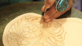 Τα χέρια ενός βιοτέχνη που σφυρηλατεί και που σφραγίζει ένα περίπλοκο floral σχέδιο επάνω στο μαύρισμα χρωμάτισαν το δέρμα απόθεμα βίντεο