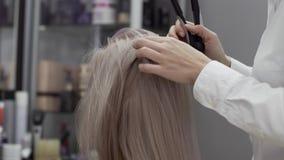 Τα χέρια ενός κομμωτή γυναικών χωρίζουν το σκέλος τρίχας του κοριτσιού πελατών απόθεμα βίντεο
