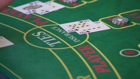 Τα χέρια ενός κρουπιέρη στον πίνακα τυχερού παιχνιδιού χαρτοπαικτικών λεσχών απόθεμα βίντεο
