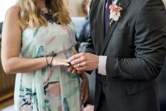 Τα χέρια ενός νεόνυμφου τελετής γάμου γαμήλιων ζευγών βάζουν το δαχτυλίδι στο δάχτυλο της καλής συζύγου του Στοκ Εικόνες