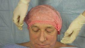 Τα χέρια ενός beautician στα γάντια βάζουν σε ένα ανθρώπινο καλλυντικό καπέλο Κινηματογράφηση σε πρώτο πλάνο απόθεμα βίντεο