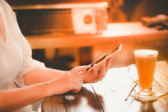 Τα χέρια εργαζόμενων γυναικών χτυπούν το έξυπνο τηλέφωνο στην εκλεκτής ποιότητας καφετερία ύφους Στοκ εικόνα με δικαίωμα ελεύθερης χρήσης