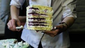 Τα χέρια ζαχαροπλαστών παρουσιάζουν μεγάλο κομμάτι του κέικ γενεθλίων απόθεμα βίντεο