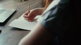 Τα χέρια καλλιτεχνών της γυναίκας επισύρουν την προσοχή με ένα μολύβι στενό σε επάνω εγγράφου φιλμ μικρού μήκους