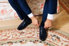 Τα χέρια κινηματογραφήσεων σε πρώτο πλάνο ενός ατόμου δένουν τις δαντέλλες στα μαύρα παπούτσια Ένας επιχειρηματίας στο μπλε παντε στοκ εικόνα