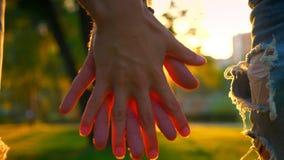 Τα χέρια κινηματογραφήσεων σε πρώτο πλάνο που κρατούν το ένα το άλλο της γυναίκας και του άνδρα, της αγάπης και της ευτυχούς απει απόθεμα βίντεο