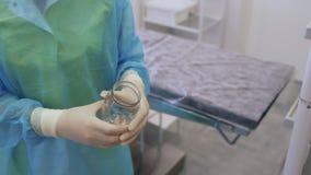 Τα χέρια κινηματογραφήσεων σε πρώτο πλάνο του γιατρού χύνουν το απολυμαντικό στο βάζο γυαλιού που κατέχει η νοσοκόμα απόθεμα βίντεο