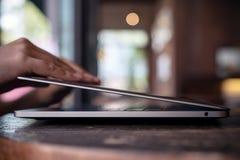 Τα χέρια κλείνουν ή ανοίγουν το lap-top στον ξύλινο πίνακα στην αρχή με το υπόβαθρο θαμπάδων bokeh Στοκ Εικόνες