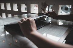 Τα χέρια κοντά και ανοίγουν έναν φορητό προσωπικό υπολογιστή στον πίνακα μετά από τελειωμένος τον στοκ φωτογραφίες