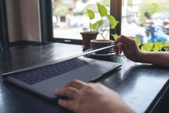 Τα χέρια κοντά και ανοίγουν έναν φορητό προσωπικό υπολογιστή στον πίνακα μετά από τελειωμένος τον στοκ φωτογραφία με δικαίωμα ελεύθερης χρήσης