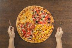 Τα χέρια κοριτσιών ` s κόβουν μια τεράστια πίτσα σε ένα κιβώτιο Τέσσερις πίτσες στο ένα Στοκ Εικόνα