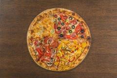 Τα χέρια κοριτσιών ` s κόβουν μια τεράστια πίτσα σε ένα κιβώτιο Τέσσερις πίτσες στο ένα Στοκ Φωτογραφία