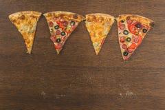 Τα χέρια κοριτσιών ` s κόβουν μια τεράστια πίτσα Τέσσερις πίτσες στο ένα Στοκ εικόνες με δικαίωμα ελεύθερης χρήσης