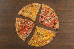 Τα χέρια κοριτσιών ` s κόβουν μια τεράστια πίτσα Τέσσερις πίτσες στο ένα Στοκ Φωτογραφίες