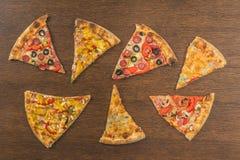 Τα χέρια κοριτσιών ` s κόβουν μια τεράστια πίτσα Τέσσερις πίτσες στο ένα Στοκ φωτογραφίες με δικαίωμα ελεύθερης χρήσης