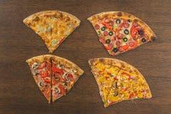 Τα χέρια κοριτσιών ` s κόβουν μια τεράστια πίτσα Τέσσερις πίτσες στο ένα Στοκ Εικόνες