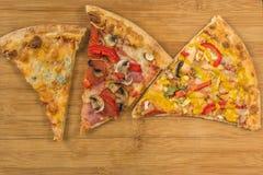 Τα χέρια κοριτσιών ` s κόβουν μια τεράστια πίτσα Τέσσερις πίτσες στο ένα Στοκ φωτογραφία με δικαίωμα ελεύθερης χρήσης