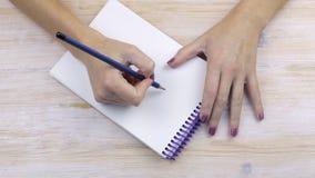 Τα χέρια κρατούν ένα μολύβι και πρόκειται να γράψουν απόθεμα βίντεο