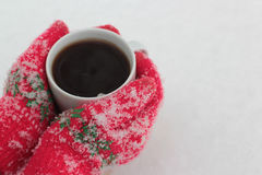 Τα χέρια κρατούν ένα φλιτζάνι του καφέ στα πλαίσια του χιονιού Στοκ Φωτογραφίες